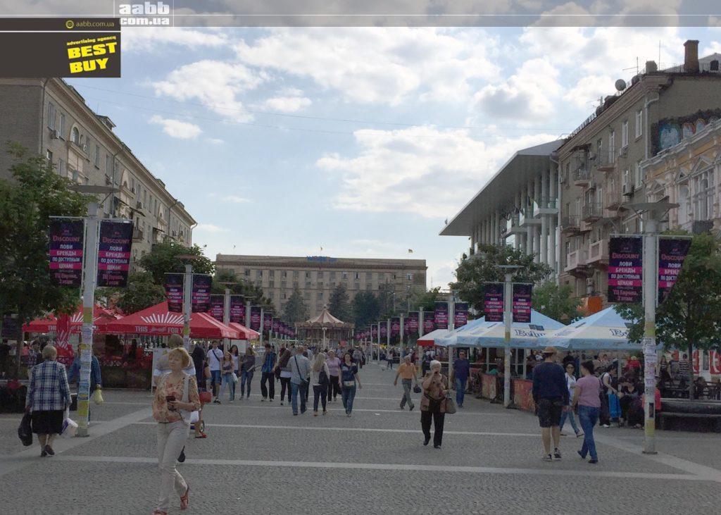 Реклама на прапорах в місті Дніпро біля ТЦ Пасаж