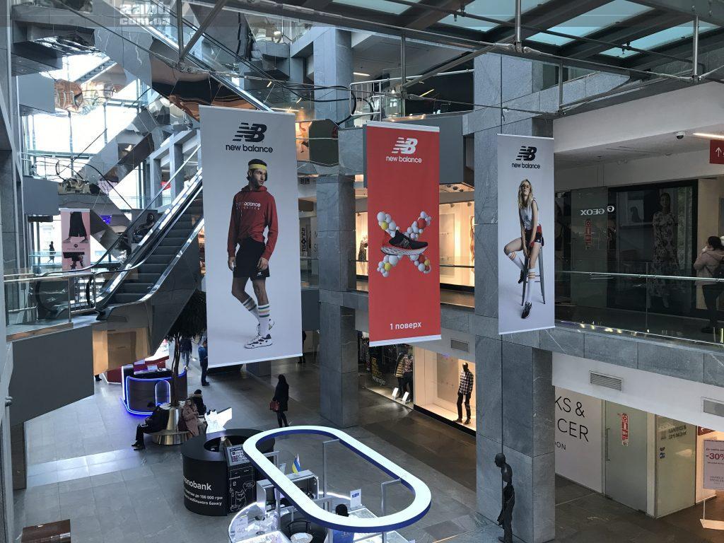 Реклама New Balance на підвісних банерах у ТЦ Пасаж
